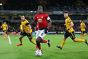 Manchester United Midfielder Paul Pogba battles with Wolverhampton Wanderers defender Matt Doherty (2) and Wolverhampton Wanderers midfielder Romain Saiss (27) during the The FA Cup match between Wolverhampton Wanderers and Manchester United at Molineux, Wolverhampton, England on 16 March 2019.