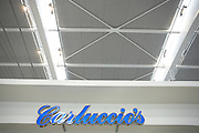 Looking upwards to Carluccio's retail sign in landside Departures area of London Heathrow Airport's Terminal 5 building