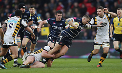 Sale's Mark Jennings is tackled by Wasps' Tommy Taylor and Thomas Young during the Aviva Premiership match at the AJ Bell Stadium, Sale.