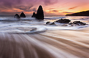 sunset at rodeo beach in the marin headlands near san francisco california. Long exposure creates streaks in the water as the wave rolls away from the shoreline.