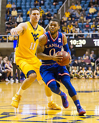 Jan 12, 2016; Morgantown, WV, USA; Kansas Jayhawks guard Frank Mason III (0) drives past West Virginia Mountaineers forward Nathan Adrian (11) during the first half at the WVU Coliseum. Mandatory Credit: Ben Queen-USA TODAY Sports