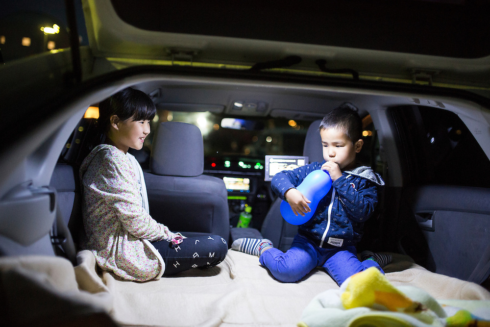 KUMAMOTO, JAPAN - APRIL 19: Misaki (9year old) watch her younger brother Kose (6year old) inside their car before going to bed in the carpark of Mashiki Gymnasium evacuation center on April 19, 2016 in Mashiki, Kumamoto, Japan. This is the fourth day in the evacuation center since magnitude-6.3 quake hit Kumamoto city.<br /> <br /> Photo: Richard Atrero de Guzman