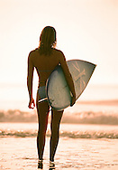 A girl getting ready to paddle out for a surf.