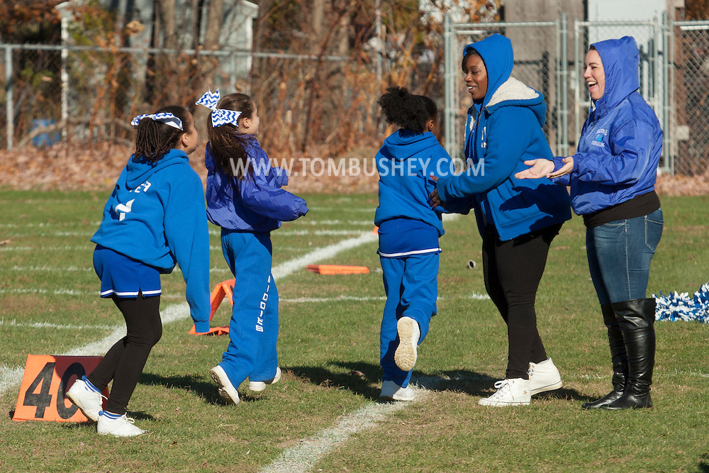 Middletown, New York - Middletown cheerleaders run off the field during an Orange County Youth Football League Division II semifinal playoff game at Watts Park on  Nov. 15, 2014.