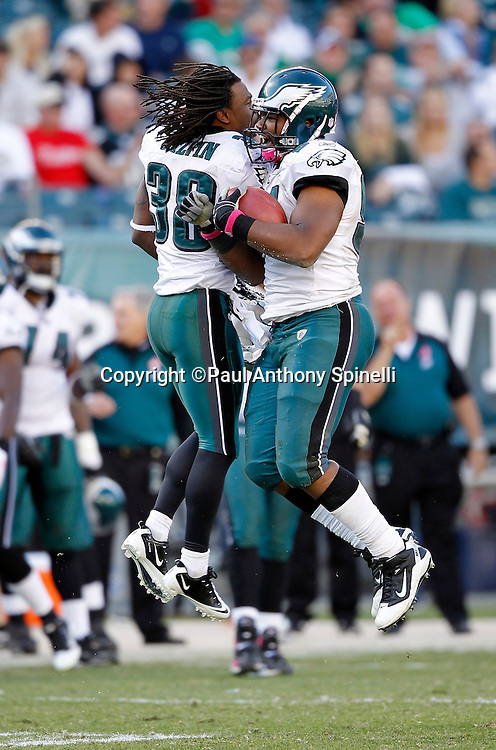 Philadelphia Eagles defensive end Darryl Tapp (91) does a hip bump with Eagles cornerback Jorrick Calvin (38) as Tapp celebrates after recovering a late fourth quarter fumble by the Atlanta Falcons during the NFL week 6 football game against the Atlanta Falcons on Sunday, October 17, 2010 in Philadelphia, Pennsylvania. The Eagles won the game 31-17. (©Paul Anthony Spinelli)