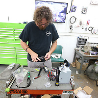 Hubbard readies a wiring harness for a head unit. Each vehicle make has a certian harness to make an aftermarket radio work properly.