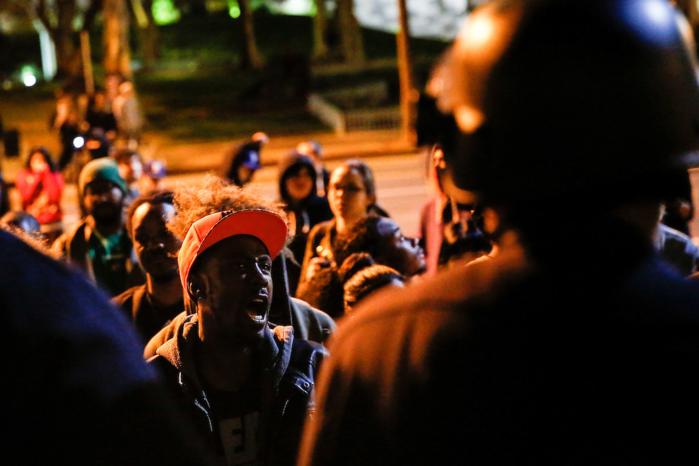 A protestor yells in the faces of LAPD officers as they hold a skirmish line in front of the LAPD Headquarters as people protest the decision of the Ferguson grand jury and the death of Michael Brown on early morning Tuesday, November 25, 2014 in Los Angeles, Calif. (Patrick T. Fallon/ For the Los Angeles Times)