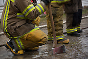 Fire fighters take a break as multiple fire departments, including Milpitas Fire Department, Spring Valley Fire Department, and Cal Fire, work to contain and extinguish a structure fire at the 3000 block of Calaveras Road near Spring Valley Golf Course in Milpitas, California, on February 10, 2014. (Stan Olszewski/SOSKIphoto)