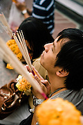 Worshippers and offerings at the Erawan Shrine