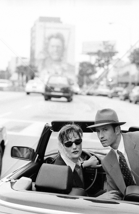 Retro couple in Hollywood, CA looking back while driving a convertible car