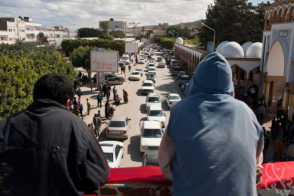 """Opposition protesters watch traffic from an overpass as they continue their """"Tahrir Square""""-style occupation of their town square February 23, 2011 in Darna, Libya. Libya tightened its grip on the capital, tripoli, but the rest of the country appeared to be slipping further out of his control. .Slug: Libya.Credit: Scott Nelson for the New York Times"""