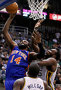 New York Knicks center Ronny Turiaf (14) attempts to score against Utah Jazz forward Paul Millsap, center, and Utah Jazz center Al Jefferson, right during the first half of an NBA basketball game in Salt Lake City, Wednesday Jan. 12, 2011. (AP Photo/Colin E Braley)