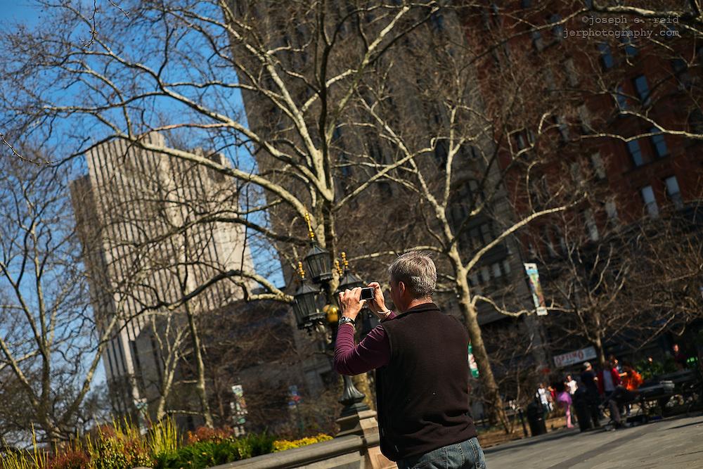 Man using compact digital camera, New York, NY, US