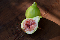 Organic, freshly picked ripe Kadota figs on a table, one fruit sliced in half showing purple pulp, artistic food still life on wood background