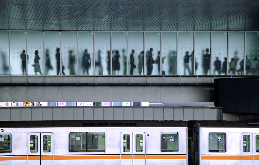 A line of commuters behind a window at Shibuya station in Tokyo with a Ginza line train below, Shibuya Station Tokyo, Japan