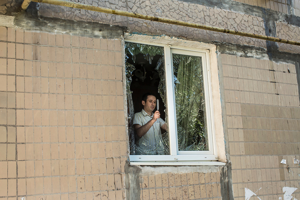 A man uses a knife to remove broken glass from the windows of his apartment after the building was hit by a suspected grad rocket strike on Tuesday, July 29, 2014 in Donetsk, Ukraine.