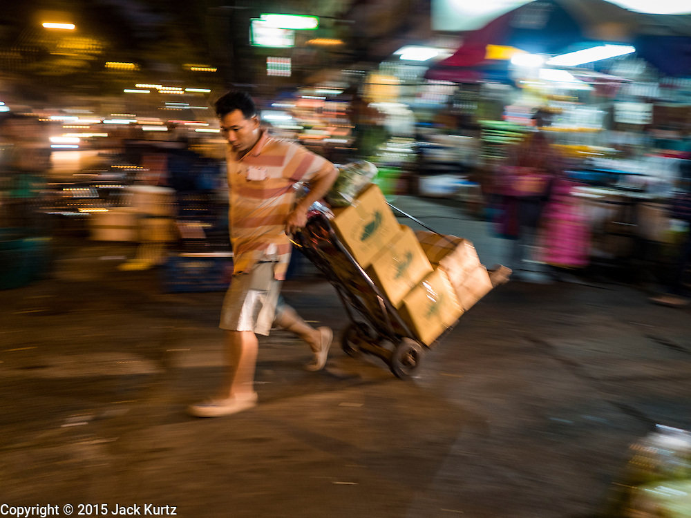 """21 DECEMBER 2015 - BANGKOK, THAILAND:  A porter hauls a load to a waiting taxi from Pak Khlong Talat, also called the Flower Market. The market has been a Bangkok landmark for more than 50 years and is the largest wholesale flower market in Bangkok. A recent renovation resulted in many stalls being closed to make room for chain restaurants to attract tourists. Now Bangkok city officials are threatening to evict sidewalk vendors who line the outside of the market. Evicting the sidewalk vendors is a part of a citywide effort to """"clean up"""" Bangkok.      PHOTO BY JACK KURTZ"""