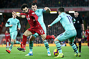 Liverpool striker Mohamed Salah (11) runs out of room under the challenge from Arsenal midfielder Granit Xhaka (34) and Arsenal midfielder Lucas Torreira (11) during the Premier League match between Liverpool and Arsenal at Anfield, Liverpool, England on 29 December 2018.