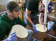 Matt Pfendler, left, and Corey Youngs fill a 3-gallon tub with Riesling ice cream at Mercer's Dairy in Boonville, New York, USA, on Friday, July 25, 2014. Mercer's is the only producer of wine ice cream, and manufactures all of its products in Boonville for distribution throughout the world. Photographer: Mike Bradley/Bloomberg