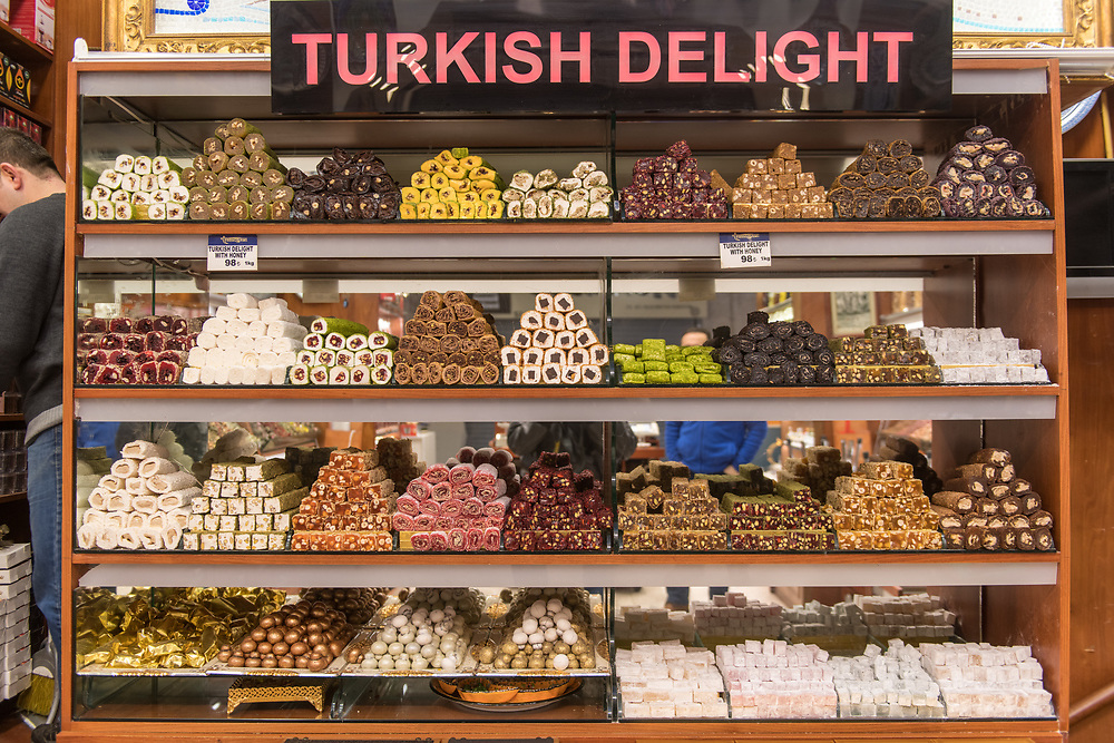 A glass case in front of shop holds an assortment of tempting Turkish delights for sale at Istanbul Spice bazaar in Turkey