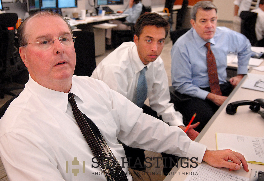 20 MAY 2010 -- ST. LOUIS -- Wells Fargo Advisors employees Bill Hein (left), of Shiloh, Ill., Cotter Smith, of St. Louis, and Jerry Grant, of St. Louis, work to resolve questions surrounding a trad while working on the trading floor at Wells Fargo Advisors in St. Louis Thursday, May 20, 2010. The company opened a new, high-tech trading floor in March. Photo © copyright 2010 Sid Hastings.