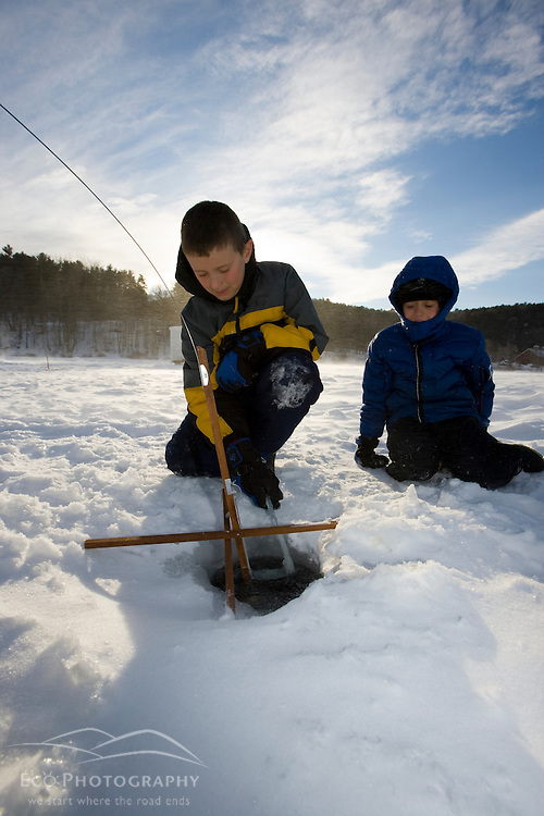 Two young brothers ice fishing on the West River in Brattleboro, Vermont.  Dad watching.