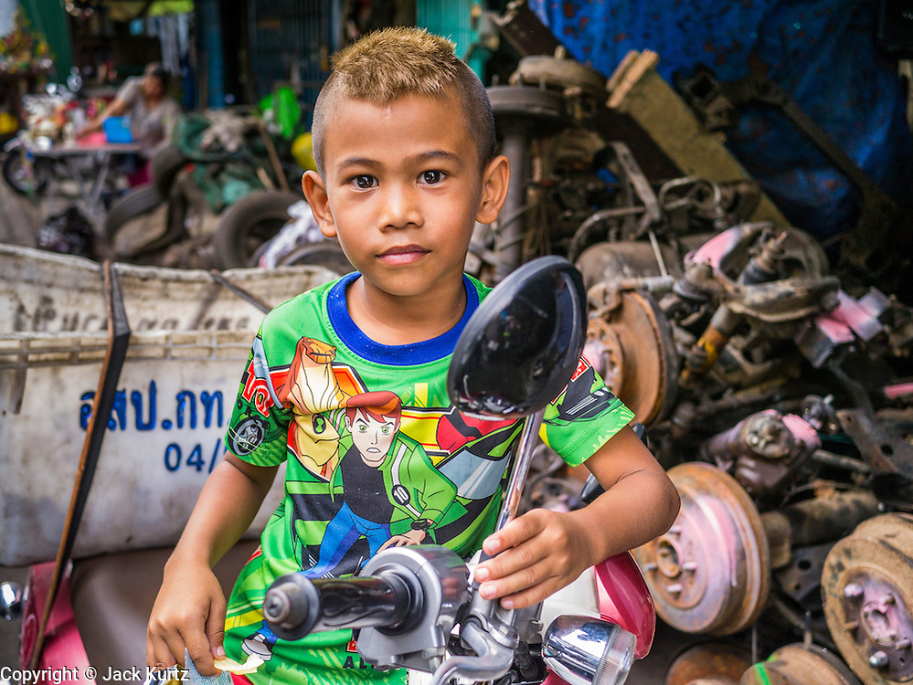 20 APRIL 2013 - BANGKOK, THAILAND:  A boy waits for his father on a motor scooter in Talat Noi (Talat means Market, Noi means Small. Literally Small Market). The Talat Noi neighborhood in Bangkok started as a blacksmith's quarter. As cars and buses replaced horse and buggy, the blacksmiths became mechanics and now the area is lined with car mechanics' shops. It is one the last neighborhoods in Bangkok that still has some original shophouses and pre World War II architecture. It is also home to a  Teo Chew Chinese emigrant community.   PHOTO BY JACK KURTZ