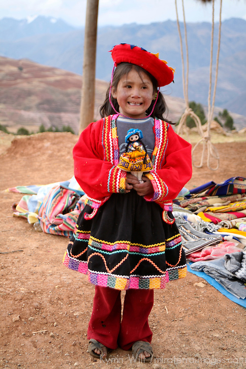Americas, South America, Peru, Urubamba. Young girl at roadside selling dolls.