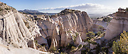 "Hoodoos panorama. See fantastic hoodoos and a great slot canyon in Kasha-Katuwe Tent Rocks National Monument, in New Mexico, USA. Hike the easy Cave Loop Trail plus Slot Canyon Trail side trip (3 miles round trip), 40 miles southwest of Santa Fe, on the Pajarito Plateau. Distinctive cone-shaped caprocks protect soft pumice and tuff beneath. Geologically, the Tent Rocks are made of Peralta Tuff, formed from volcanic ash, pumice, and pyroclastic debris deposited over 1000 feet thick from the Jemez Volcanic Field, 7 million years ago. Kasha-Katuwe means ""white cliffs"" in the Pueblo language Keresan. This panorama was stitched from 7 overlapping photos."