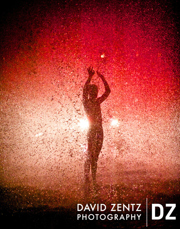 A man dances in a downpour caused by a damaged fire hydrant in Venice, Calif.