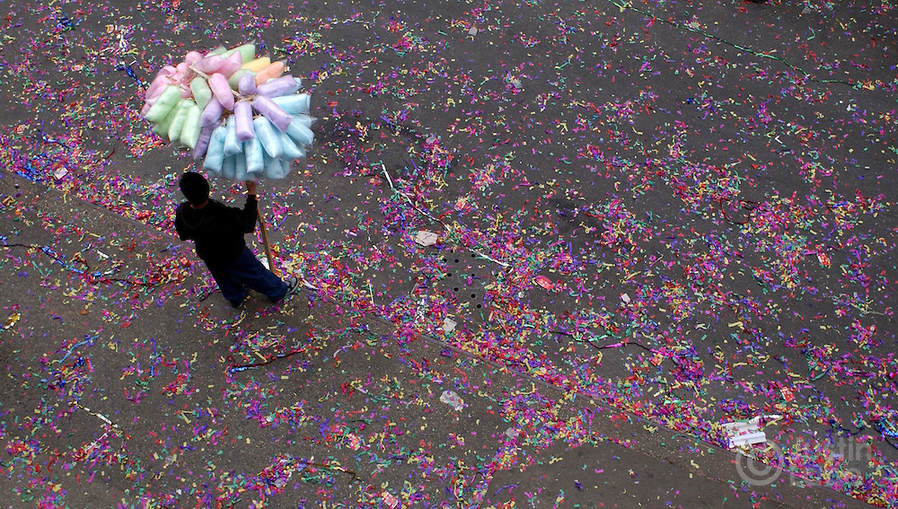 A man selling cotton candy is seen on a street covered with confetti as result of Chinese New Year celebrations in Chinatown Wednesday 9 February 2005 in New York.