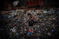 A woman searching for cans in a slum, Phnom Penh, Cambodia.<br />