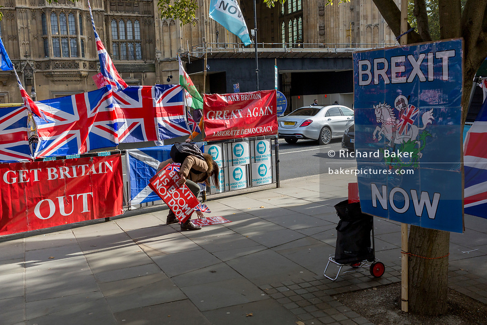 On the day that the EU in Brussels agreed in principle to extend Brexit until 31st January 2020 (aka 'Flextension') and not 31st October 2019, a Brexiteer picks up dropped placards next to Brexit Party flags and banners during a Brexit protest outside parliament, on 28th October 2019, in Westminster, London, England.