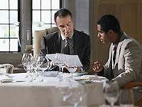 Two business men sitting at restaurant table analyzing documents