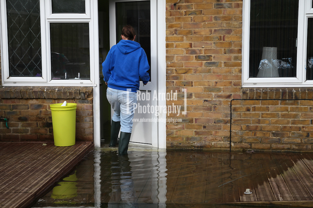 24/02/2014. Basingstoke, Hampshire, UK. Kirsty Campbell (23) entering her house on Sperrin Close which she and her family have had to evacuate due to groundwater flooding in the Buckskin area of Basingstoke, Hampshire. Groundwater levels are continuing to rise in the area, forcing 69 homes to be evacuated in the Buckskin Area of the commuter town. Photo by Rob Arnold