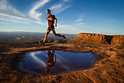A trail runner runs along the canyon rim in Canyonlands National Park in the morning.