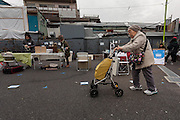 An older woamn walks through a small park where a flea market is being set up in Shimo Kitazawa, Tokyo, Japan. Sunday January 8th 2017
