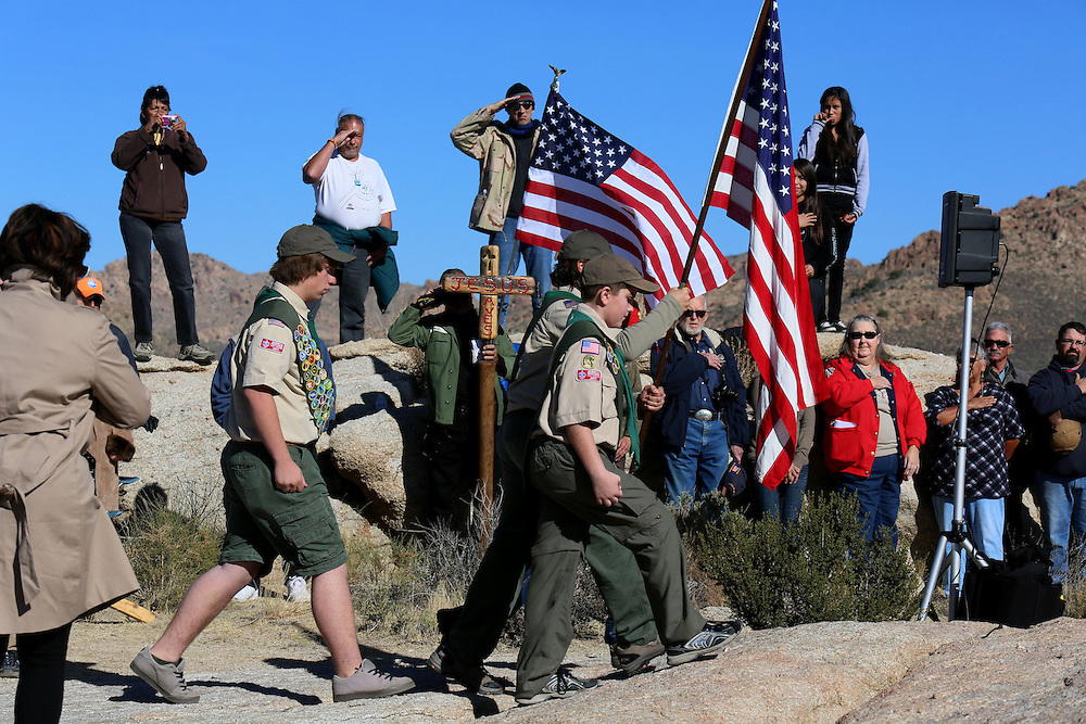 Boyscout Colorguard present the flag during an unveiling ceremony for the Mojave Cross on Veterans Day in Cima, California on Sunday, November 11, 2012.  A battle has been brewing for over Thirteen years over whether the cross can legally stay on Sunrise Rock because it violates Separation of Church and State and is in the Mojave National Perserve which is on Federal Lands.  The Veterans of Foreign Wars and American Legion Society raised money to purchase the plot of land and has kept the cross in place and today serves as war memorial.(Photo by Sandy Huffaker)