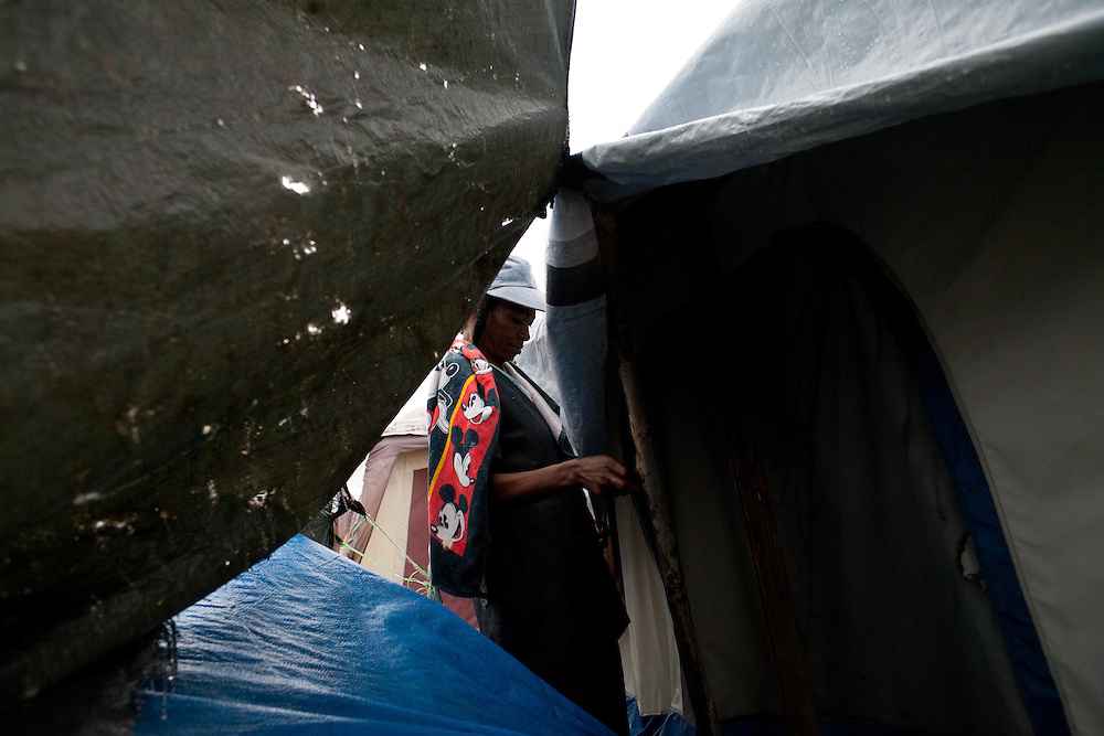 A camp resident repairs her tarp shelter after heavy winds and rain from hurricane Tomas.
