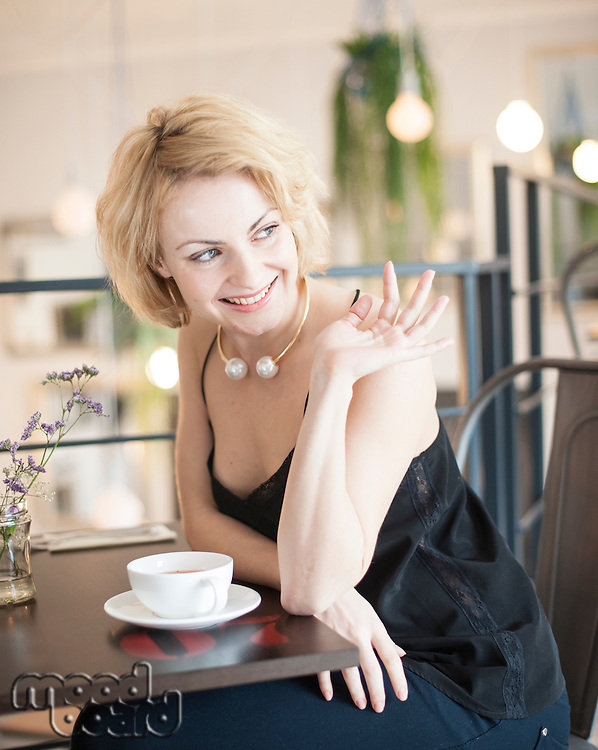 Happy young woman waving at restaurant table