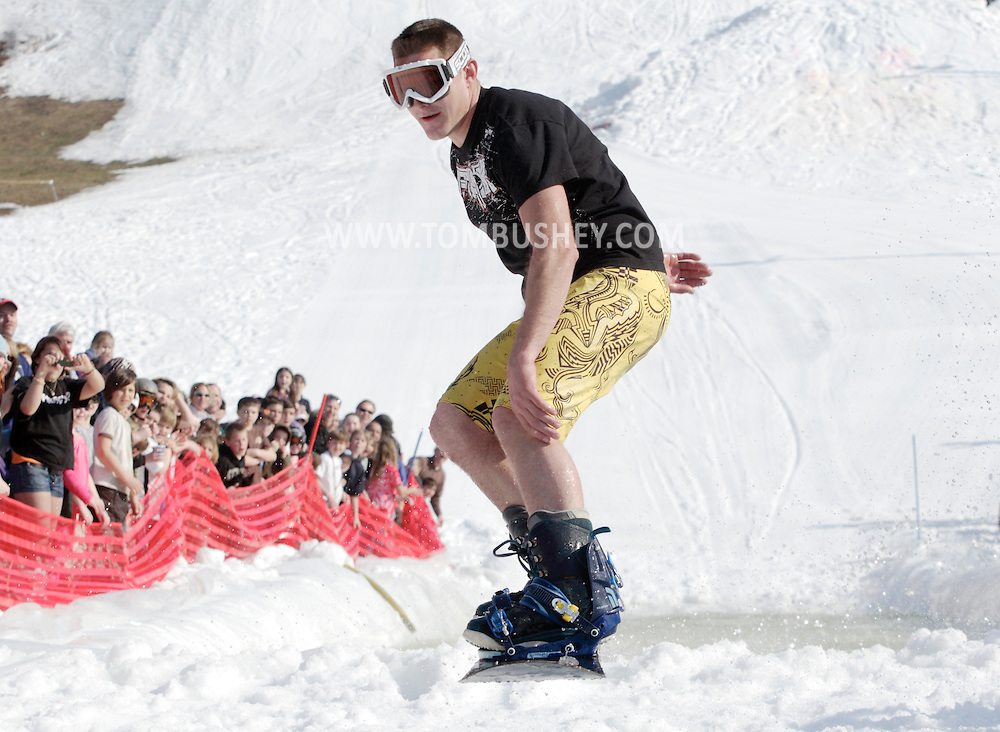 Warwick, New York - A snowboarder in shorts and tee shirt flies through the air after crossing the water during the annual Spring Rally at Mount Peter Ski and Ride on March 21, 2010.