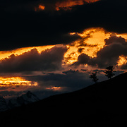 Malachi Artise rides a ridge as the clouds glow orange in the Tetons.