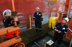 PDVSA workers Rangel Loazdo(right) , Juan Franco(center) and Juan Hernandez work on an offshore crude oil loading platform at the Jose complex.