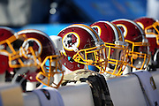 A string of Washington Redskins helmets sit on sideline bench during the playing of the National Anthem before the 2015 week 9 regular season NFL football game against the New England Patriots on Sunday, Nov. 8, 2015 in Foxborough, Mass. The Patriots won the game 27-10. (©Paul Anthony Spinelli)