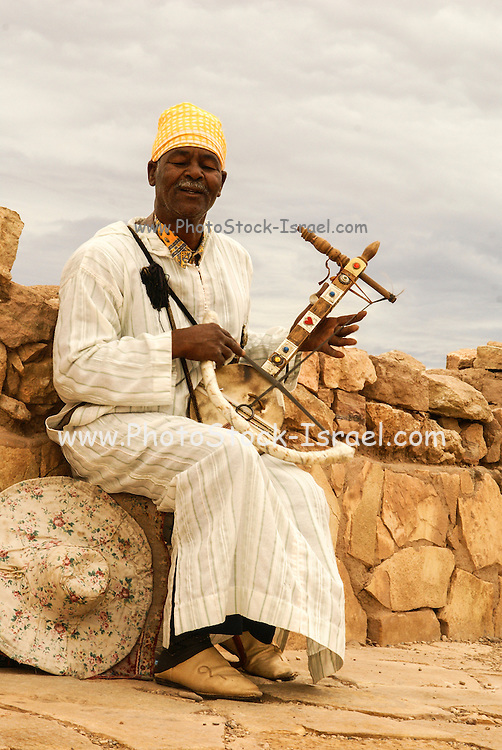Local man plays traditional Berber amzhad a single string musical instrument in Kasbah Ait Benhaddou, Morocco