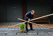 An elderly man lifts two bamboo poles that were lying in front of his storefront.