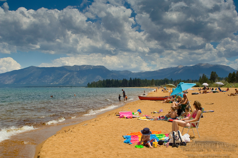 Family enjoying sand and clear water at Baldwin Beach below blue sky, clouds, and mountains, South Lake Tahoe, California