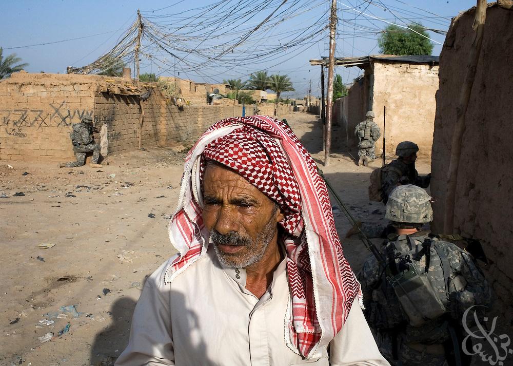 An Iraqi man watches as U.S. Army 1-23 Strykers soldiers patrol through the Mufrek neighborhood of Bacouba, Iraq June 21, 2007. ..