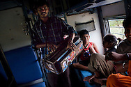 A man plays music as he duets Hindi love songs with his wife (unseen) who then begs for money while cradling her child. They get on the Himsagar Express 6318 at Erode Junction and get off at Coimbatore Junction on 9th July 2009.. .6318 / Himsagar Express, India's longest single train journey, spanning 3720 kms, going from the mountains (Hima) to the seas (Sagar), from Jammu and Kashmir state of the Indian Himalayas to Kanyakumari, which is the southern most tip of India...Photo by Suzanne Lee / for The National