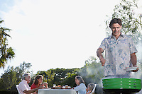 Man grilling people sitting at table in background